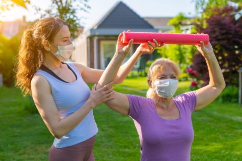 Younger woman instructing elderly woman during a workout