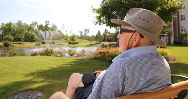 Elderly man sitting on a bench overlooking a lake