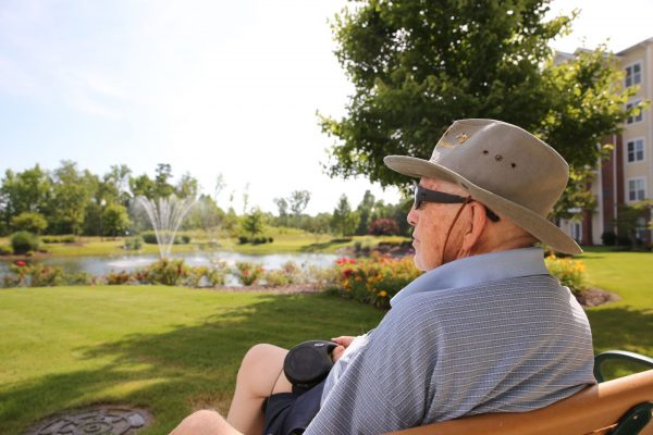 Elderly man sitting on a bench overlooking a lake with fountain