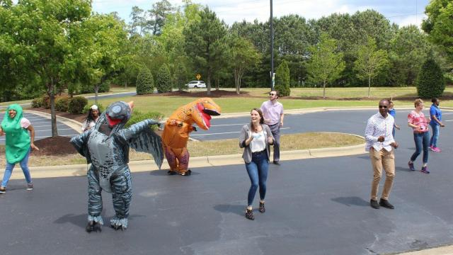 Group of people dressed up in costumes dancing in a parking lot