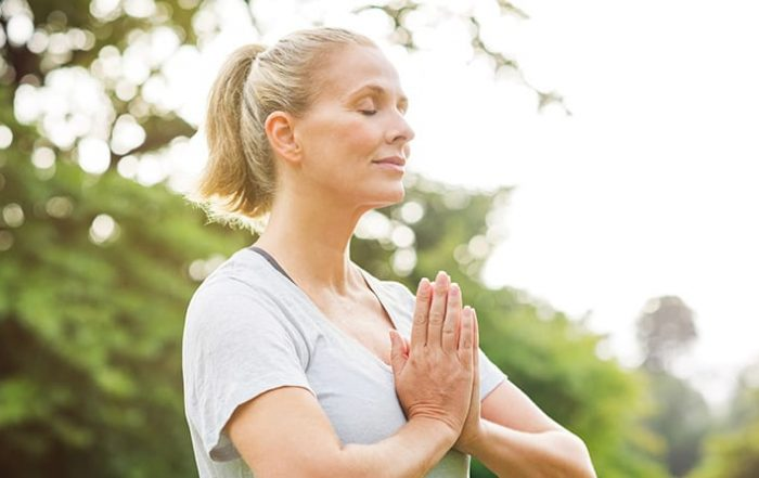 Woman standing with her hands over her heart meditating