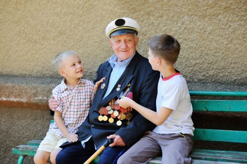 Two young children sitting with an elderly veteran